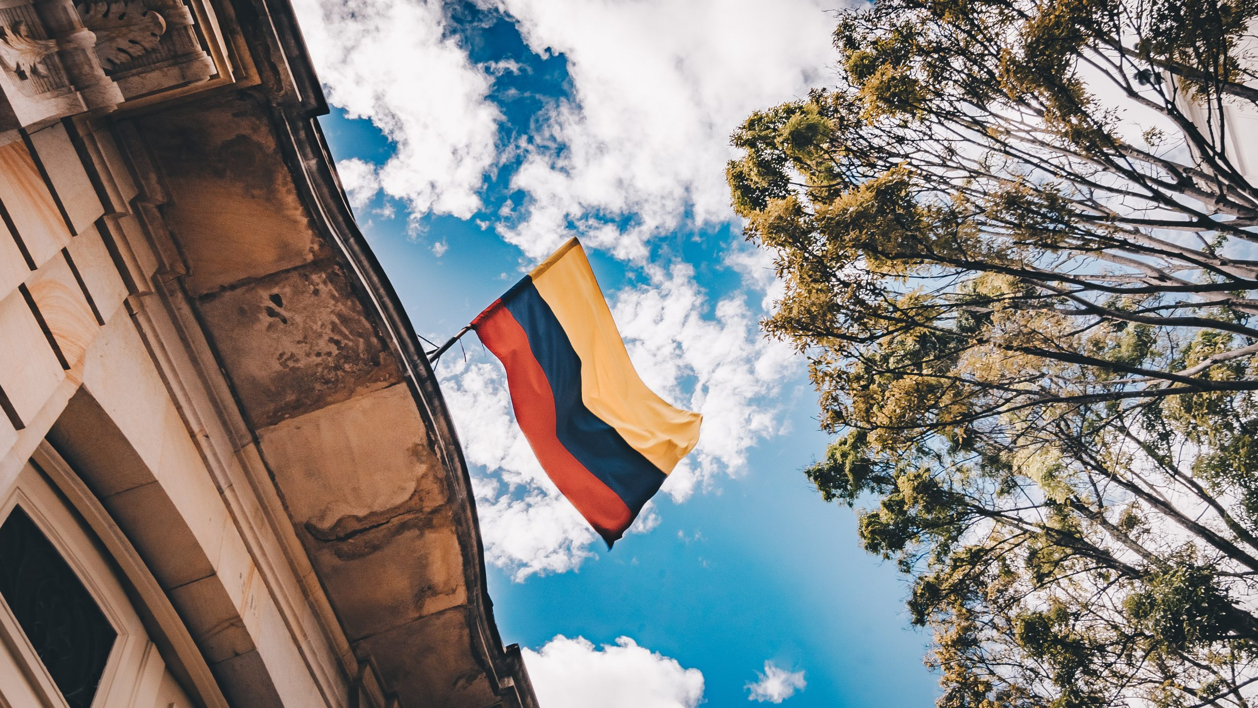 A Colombian flag atop a building from below