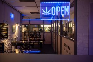 "A lit sign with a picture of a marijuana leaf and the word ""open"" hung outside of a dispensary."