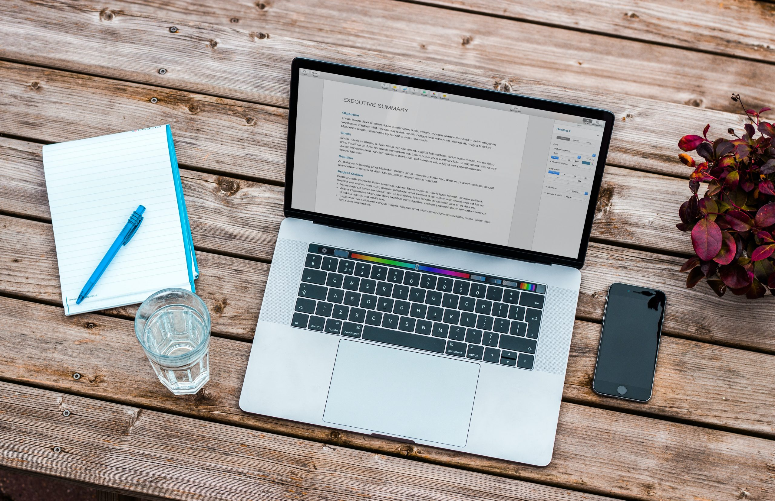 A top down view of a laptop on a table with a phone, glass of water and notebook beside it.