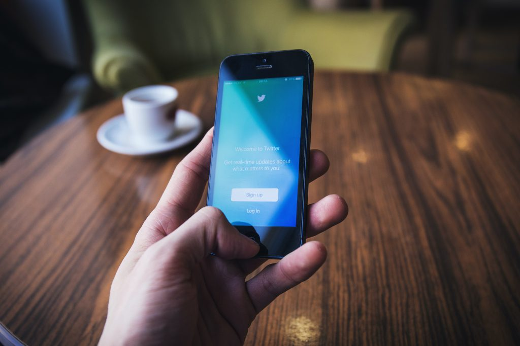 A person's hand holding a smartphone with Twitter on the screen in front of a table with a cup of coffee on it.