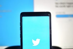 A photo of a smartphone displaying the Twitter logo in front of a blurred computer screen in the background.