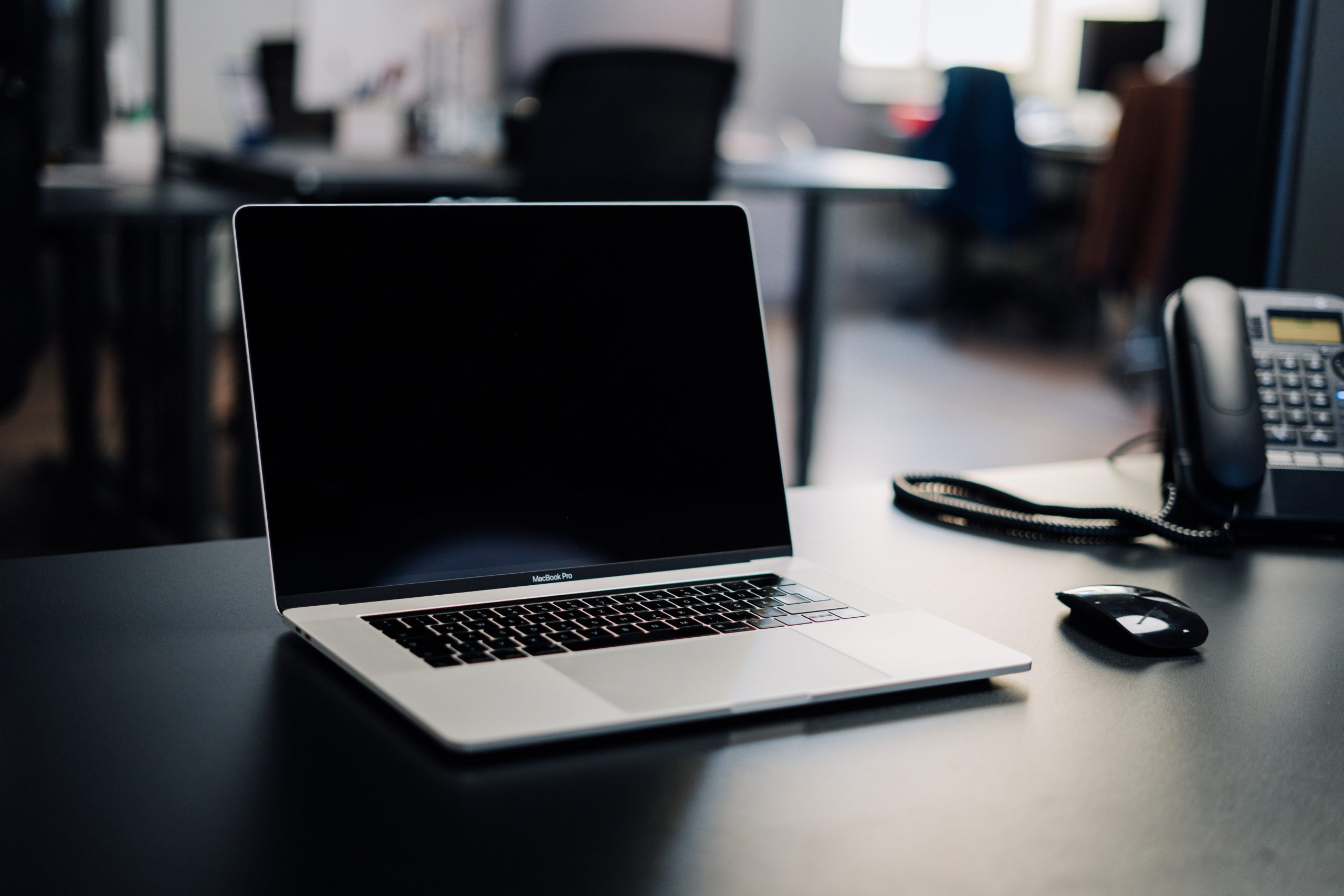 A MacBook sitting on a desk next to a mouse and a desk phone, with a blurred office background