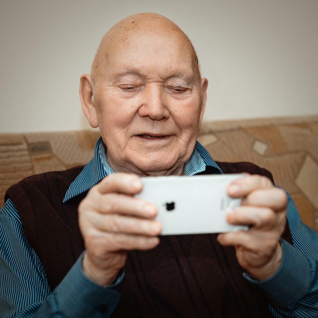 An older man holding a smartphone
