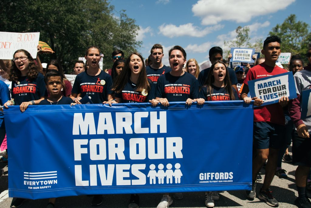 a group of protesters behind a sign that reads 'march for our lives'