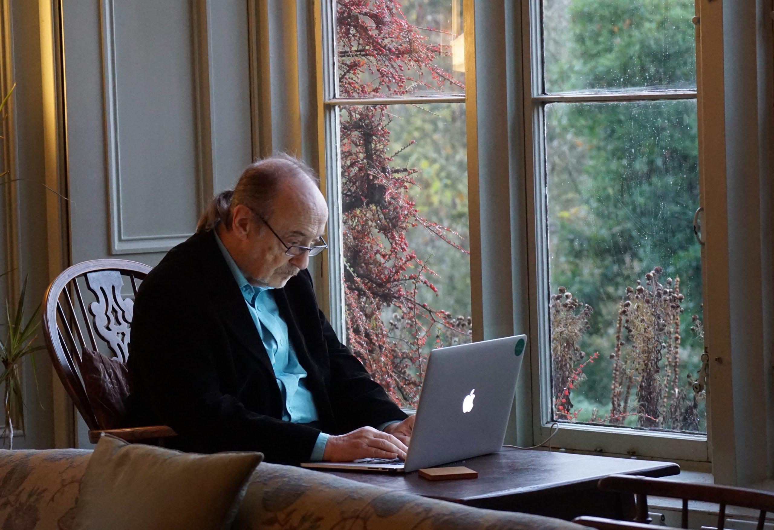 an older man working at a laptop
