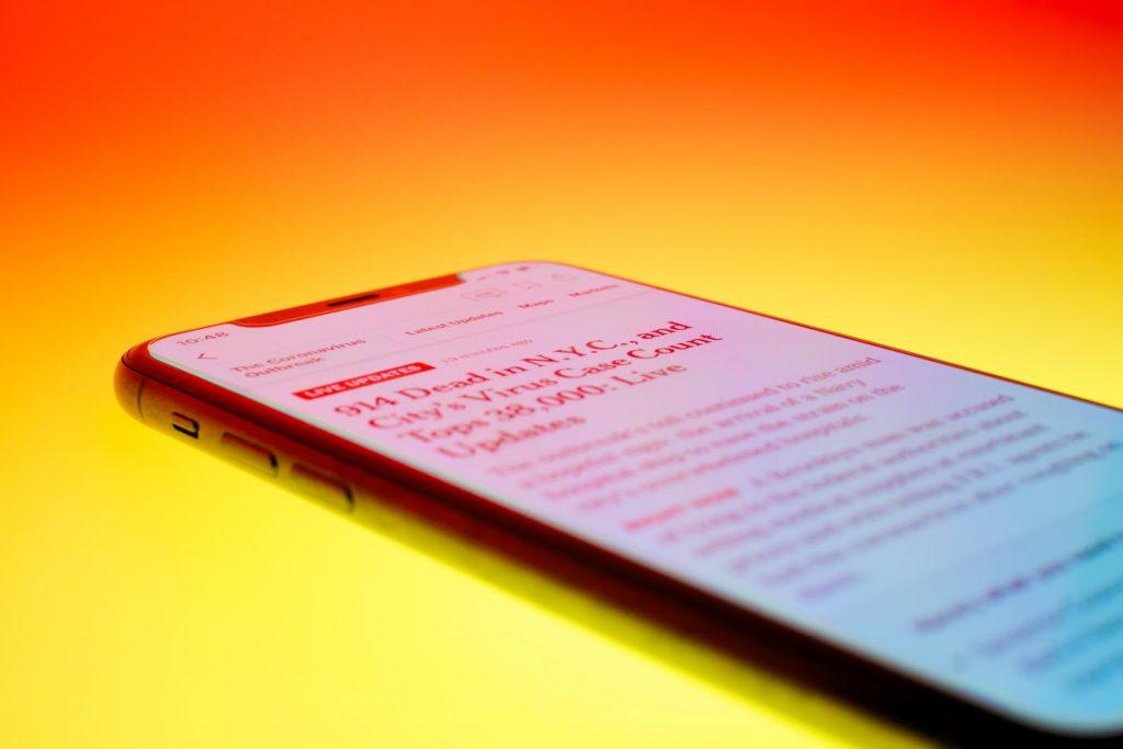 A news headline on a smartphone on an orange background