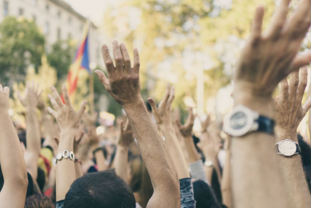 A group of people with their hands raised in the air