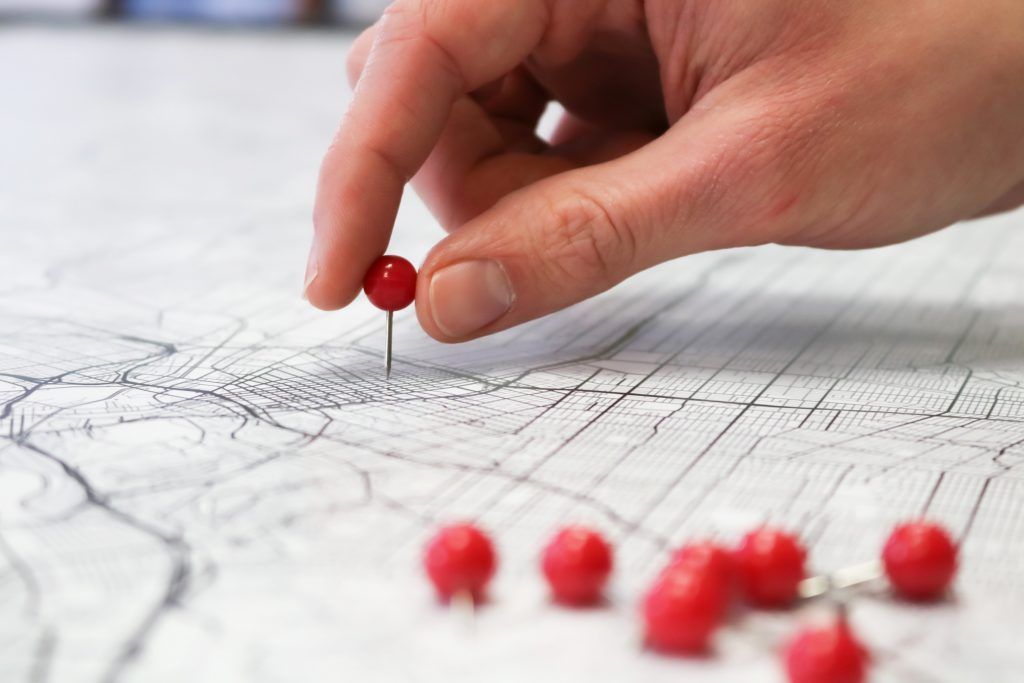 Placing red push pins into city street map.