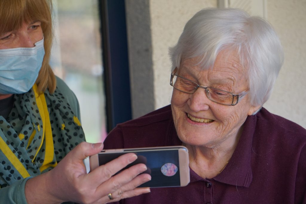An older woman looking at a smartphone being held by a younger woman wearing a mask