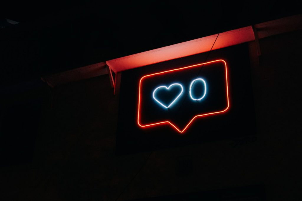 A neon sign in the shape of a speech bubble with a heart and the number 0 inside of it.