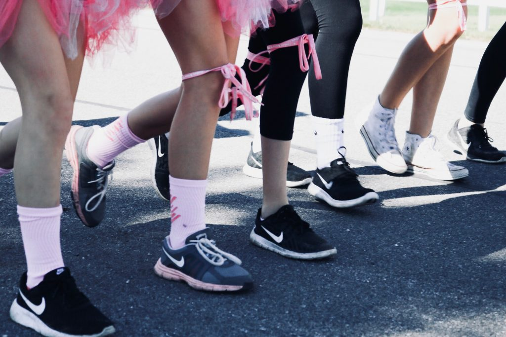 Several people's legs with pink decorations participating in a breast cancer walk
