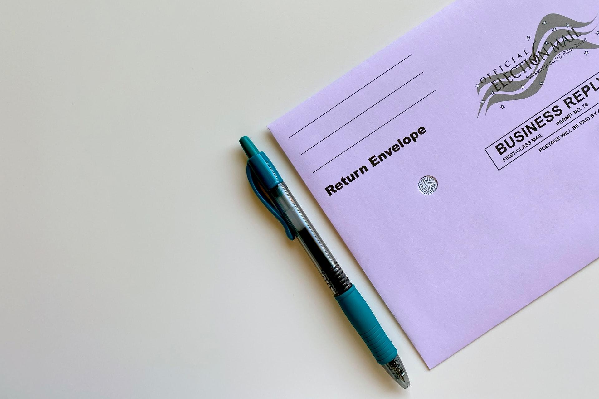 An absentee ballot envelope and a pen